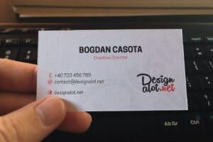 Business-Card-Mockup-Held-In-Hand-Above-Keyboard-designalot